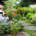 Deutschland, Tee trinkende Seniorin sitzt am Tisch in einem sommerlichen Garten.